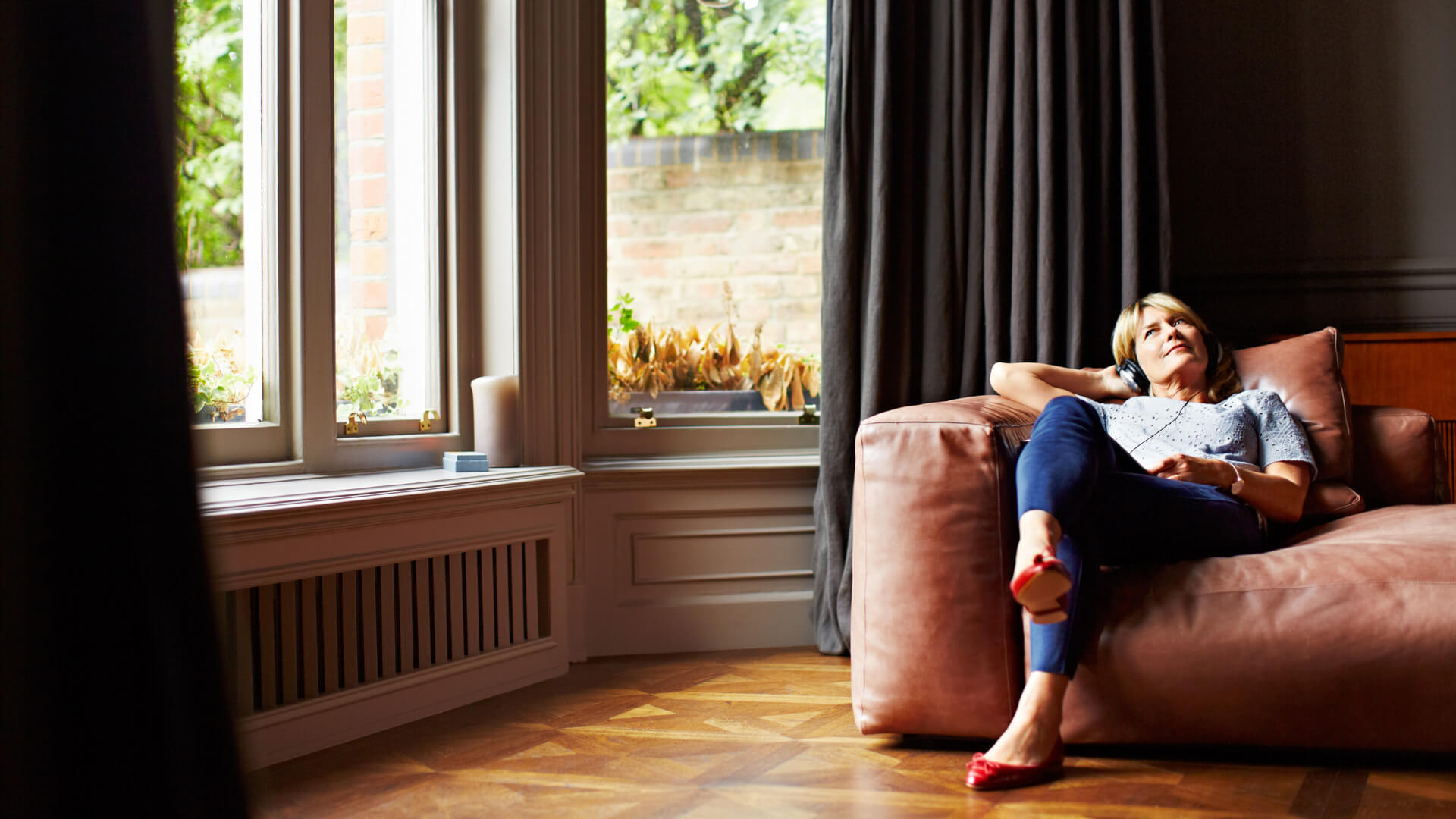 Woman On Sofa With Bay Window Listening To Music
